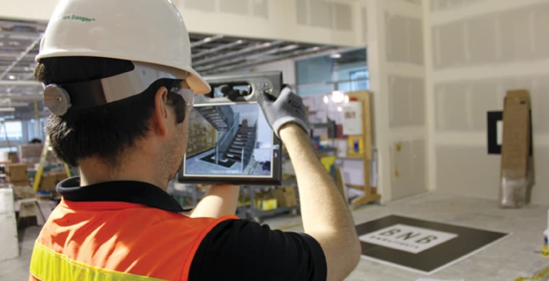 Worker using tablet with Augmented Reality in a site