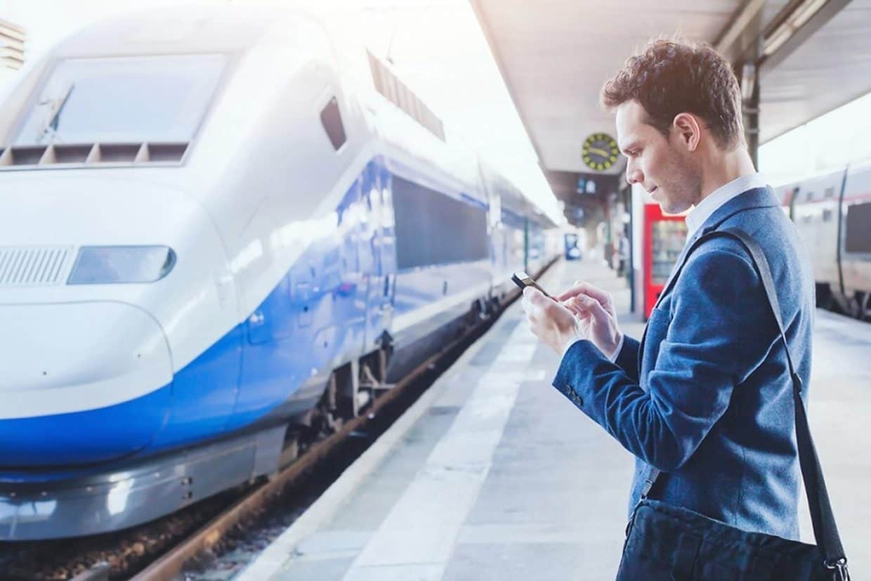Man using smartphone in a train station